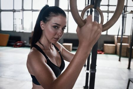 Happy healthy athletic woman laughing, resting after gymnastic rings workout