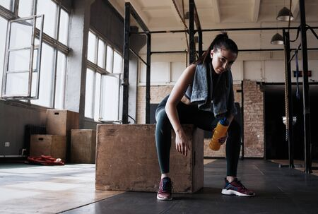 Fitness woman sitting on a box at gym after her workout. Banco de Imagens