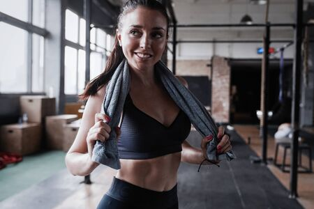 Woman with fit body standing at gym with towel around her neck
