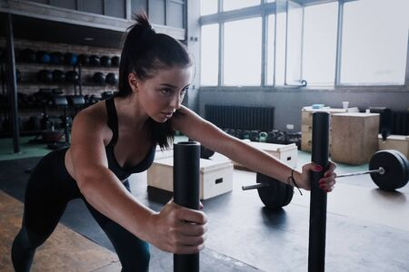 Fit female athlete working out in the gym. Crossfit woman exercising