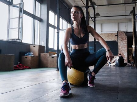 Motivated female workout fitness club, sit gym smile camera, wipe sweat off forehead, lean medicine ball crossfit Stock Photo