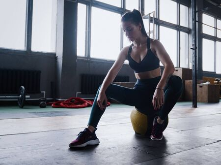 Motivated female workout fitness club, sit gym smile camera, wipe sweat off forehead, lean medicine ball crossfit