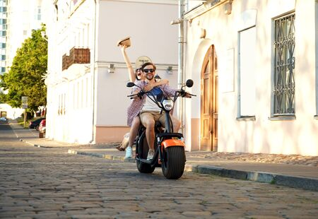 Couple in love riding a motorbike , Handsome guy and young sexy woman travel . Young riders enjoying themselves on trip. Adventure and vacations concept. Stock Photo