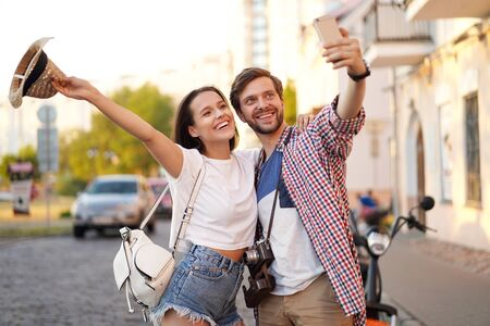 Happy couple of tourists photographing a selfie in a city street in a sunny day.