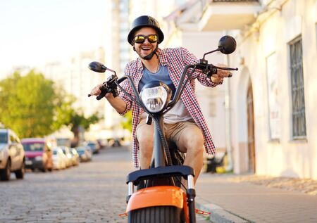 fashionable young man riding a orange motorbike in the street. Imagens