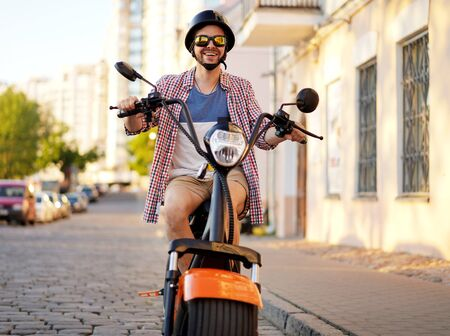 fashionable young man riding a orange motorbike in the street. Stok Fotoğraf