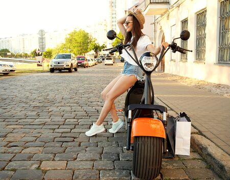 Portrait of a beautiful girl sitting on a orange motorbike, smiling and looking at the camera. Reklamní fotografie