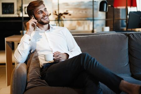 Happy businessman sitting and talking on the phone at office.