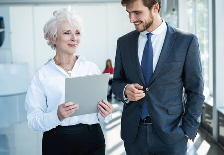 Senior mature caucasian female executive ceo discuss report with young colleague Stock Photo