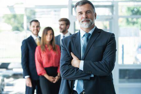 Stolzer lächelnder Geschäftsmann, der mit seinen Kollegen im Büro steht Standard-Bild