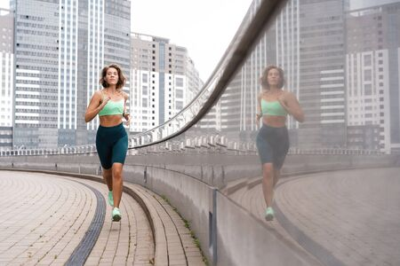 Sporty young woman athlete running on urban street in morning.