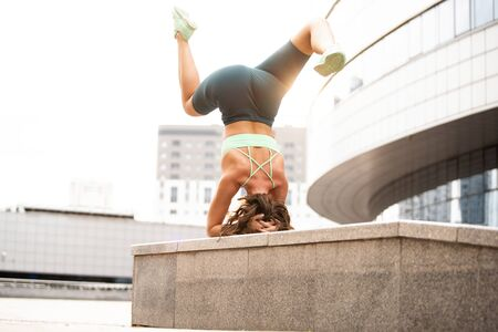 Yoga in the city: woman doing stretching workout standing head down on her hands.