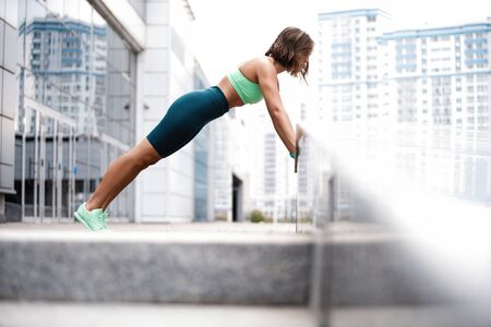 Fit young woman doing plank exercise outdoor in urban environment