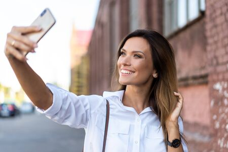Outdoors lifestyle portrait of pretty young woman making selfie by the phone walking on the city