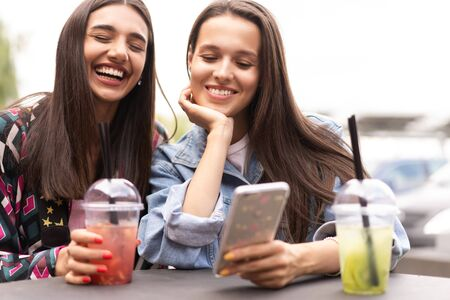Young girls friends watch something in smartphone. Фото со стока - 133398384