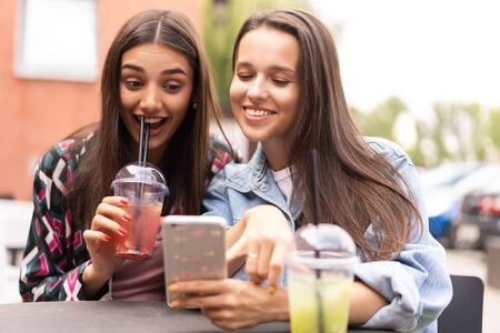 Young girls friends watch something in smartphone.