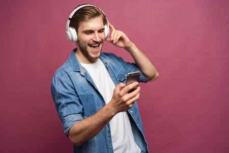 Excited young man standing isolated over pink background, listening to music with earphones and mobile phone Standard-Bild - 133245326