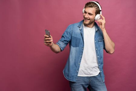 Excited young man standing isolated over pink background, listening to music with earphones and mobile phone