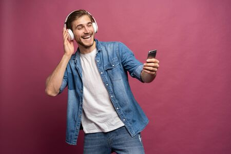 Excited young man standing isolated over pink background, listening to music with earphones and mobile phone Standard-Bild - 133247254