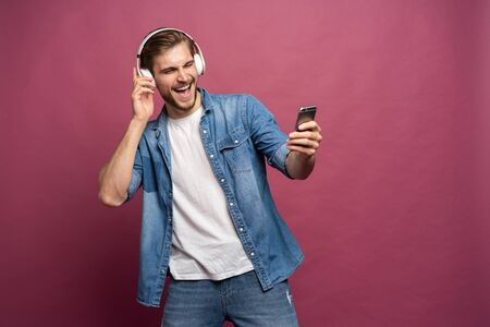 Excited young man standing isolated over pink background, listening to music with earphones and mobile phone Standard-Bild - 133244610