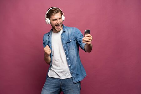 Excited young man standing isolated over pink background, listening to music with earphones and mobile phone Standard-Bild - 133244650