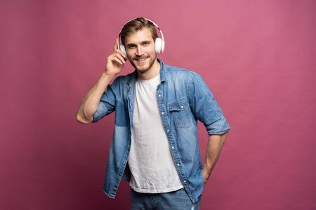 Portrait of happy young man listening to music with headphones isolated over pink background. Standard-Bild - 133245018