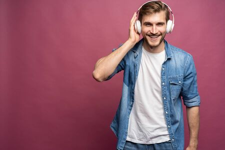 Portrait of happy young man listening to music with headphones isolated over pink background. Standard-Bild - 133247535