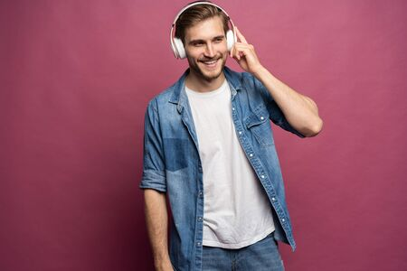Portrait of happy young man listening to music with headphones isolated over pink background. Standard-Bild - 133244372