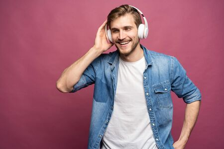 Portrait of happy young man listening to music with headphones isolated over pink background. Standard-Bild - 133245073