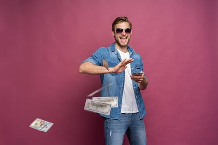 Concept of financial wealth, prosperity and lottery winnings - Man throwing away his money isolated over pink