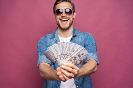 Portrait of a cheerful man holding dollar bills over pink background. Stock Photo