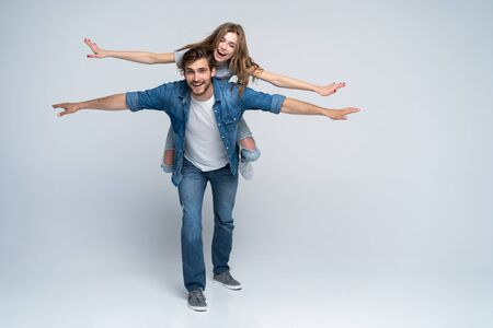 Cute portrait of couple. Guy rolls a girl on his back. Stock Photo
