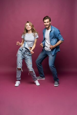 Active young couple of friends having good time, dancing, laughing together on pink background Stock Photo