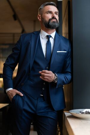 Stylish bearded man in a suit standing in modern office Stock fotó