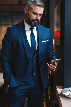 Formally dressed male executive manager in trendy clothes using mobile phone