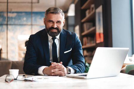 człowiek biznesu pracujący z dokumentami i laptopem