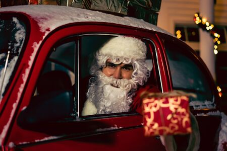 Merry Christmas and Happy Holiday! Santa Claus sitting in car with christmas present looking at camera