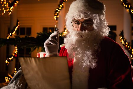Happy Santa Claus reading Christmas letter outdoors near his red car