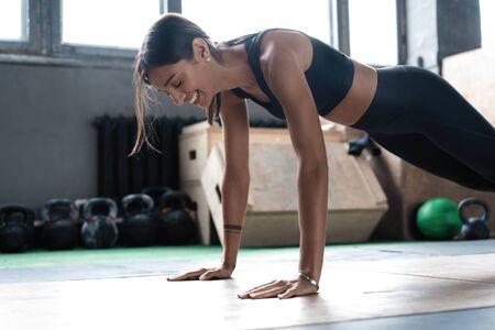 Mujer haciendo tablones en el piso del gimnasio. Concepto de estilo de vida saludable