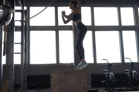 Fit young woman box jumping at a crossfit style gym. Female athlete is performing box jumps at gym Stock fotó