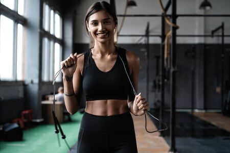 Fit and healthy woman standing at gym with skipping rope. Sportswoman resting after workout.