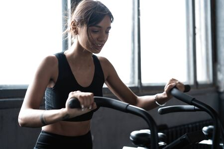 Fit young woman using exercise bike at the gym. Fitness female using air bike for cardio workout at gym Imagens