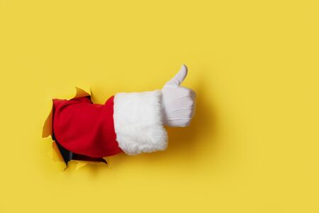 Santa Claus hand showing thumb up isolated on yellow