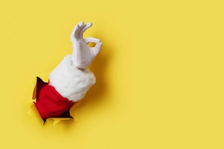 Santa Claus hand showing OK isolated on yellow 版權商用圖片 - 135632827