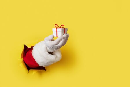 Santa Holding Small Gift Box in his hand isolated over yellow - hand and arm only 写真素材