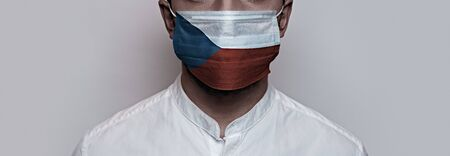 Corona virus pandemic. Concept of Corona virus quarantine, Covid-19. The male face is covered with a protective medical mask, painted in Czech Republic flag colors