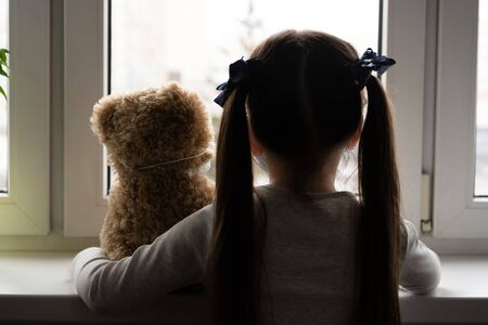 Stay at home quarantine coronavirus pandemic prevention. Sad child and his teddy bear both in protective medical masks sits on windowsill and looks out window. COVID-2019 disease concept