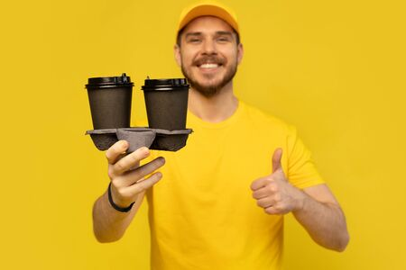 Portrait of cheerful delivery man in yellow uniform smiling and holding takeaway coffee cups isolated over yellow Reklamní fotografie