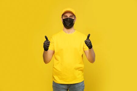 Delivery man in yellow cap, t-shirt uniform, mask gloves isolated on yellow background. Coronavirus 2019-ncov concept Фото со стока