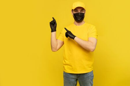 Delivery man in yellow cap, t-shirt uniform, mask gloves isolated on yellow background. Coronavirus 2019-ncov concept Фото со стока - 146386193